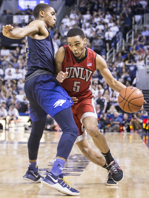 UNLV's Jalen Poyser (5) tries to turn the corner past UNR's Josh Hall (33) during the Rebel's road matchup with the Wolf Pack on Wednesday, Feb. 8, 2017, at the Lawlor Events Center, in Reno. (Ben ...