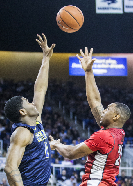 UNLV's Christian Jones (20) shoots a jump hook over UNR's Cameron Oliver (0) during the Rebel's road matchup with the Wolf Pack on Wednesday, Feb. 8, 2017, at the Lawlor Events Center, in Reno. (B ...