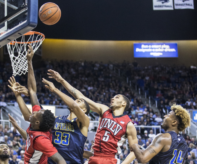 UNLV's Jalen Poyser (5) fights for a loose ball with UNR's Josh Hall (33) during the Rebel's road matchup with the Wolf Pack on Wednesday, Feb. 8, 2017, at the Lawlor Events Center, in Reno. (Benj ...