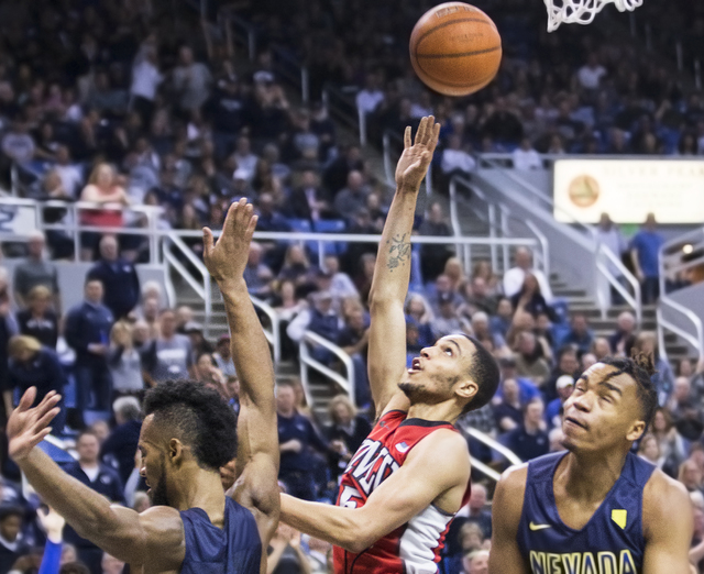 UNLV's Jalen Poyser (5) slashes to the rim past UNR's Leland King II (2) and D.J. Fenner (15) during the Rebel's road matchup with the Wolf Pack on Wednesday, Feb. 8, 2017, at the Lawlor Events Ce ...