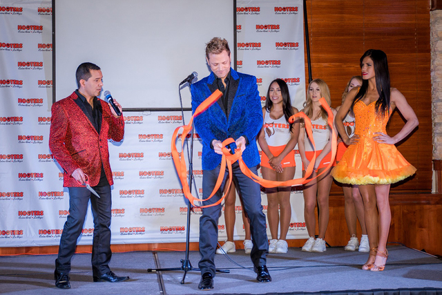 The comedy team of Jarrett & Raja (that's Raja with the scissors) take part in a ribbon-cutting ceremony at Hooters hotel-casino on Monday, Jan. 23, 2017. (Julie Bergonz)