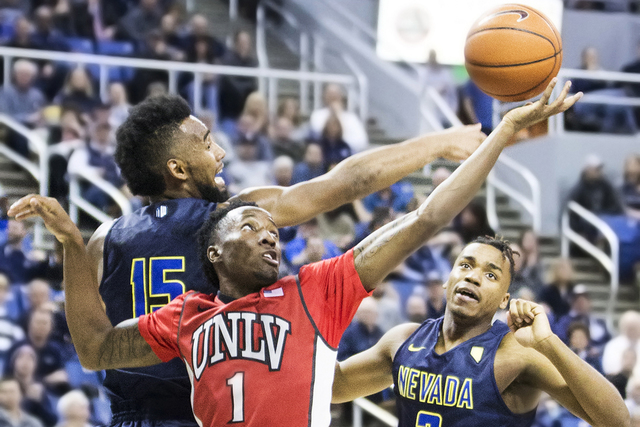 UNLV's Kris Clyburn (1) reaches for a loose ball over  UNR's D.J. Fenner (15) and Leland King II (2) during the Rebels' road matchup with the Wolf Pack on Wednesday, Feb. 8, 2017, at the Lawlor Ev ...