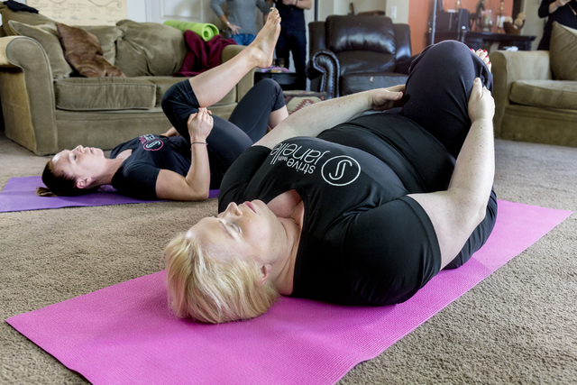 """Janelle Brown, right, creator of STRIVE with Janelle and star of TLC's """"Sister Wives,"""" warms up with Markie Henderson, personal trainer, for a filming for STRIVE, the online fitness community, in  ..."""