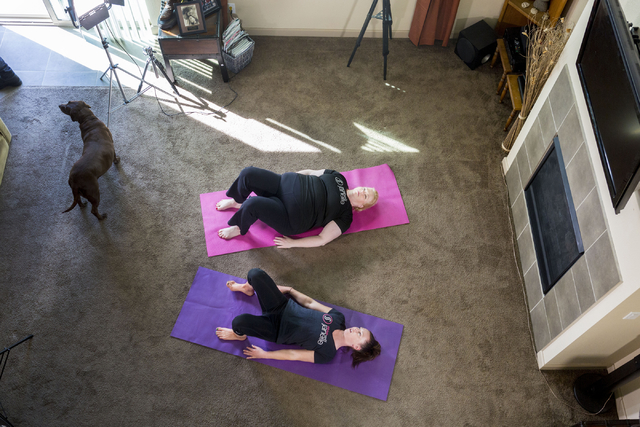 """Janelle Brown, top, creator of STRIVE with Janelle and star of TLC's """"Sister Wives,"""" warms up with Markie Henderson, personal trainer, for a filming for STRIVE, the online fitness community, in Br ..."""
