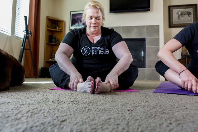 """Janelle Brown, center, creator of STRIVE with Janelle and star of TLC's """"Sister Wives,"""" warms up with Markie Henderson, personal trainer, for a filming for STRIVE, the online fitness community, in ..."""