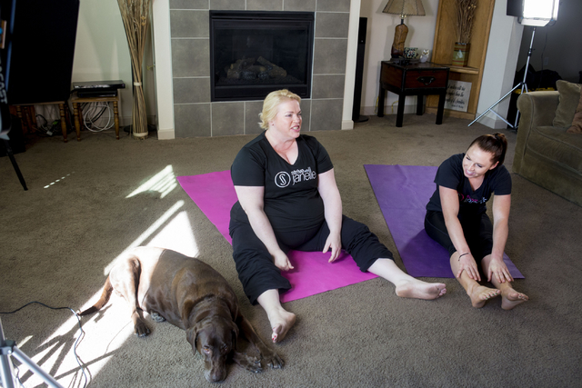 """Janelle Brown, left, creator of STRIVE with Janelle and star of TLC's """"Sister Wives,"""" warms up with Markie Henderson, personal trainer, for a filming for STRIVE, the online fitness community, in B ..."""