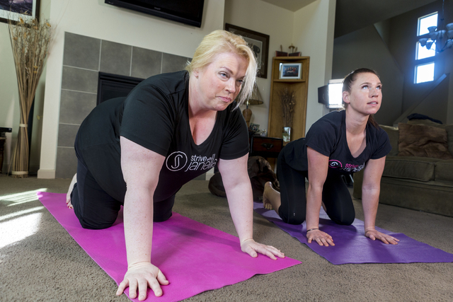 "Janelle Brown, left, creator of STRIVE with Janelle and star of TLC's ""Sister Wives,"" warms up with Markie Henderson, personal trainer, for a filming for STRIVE, the online fitness community, in B ..."