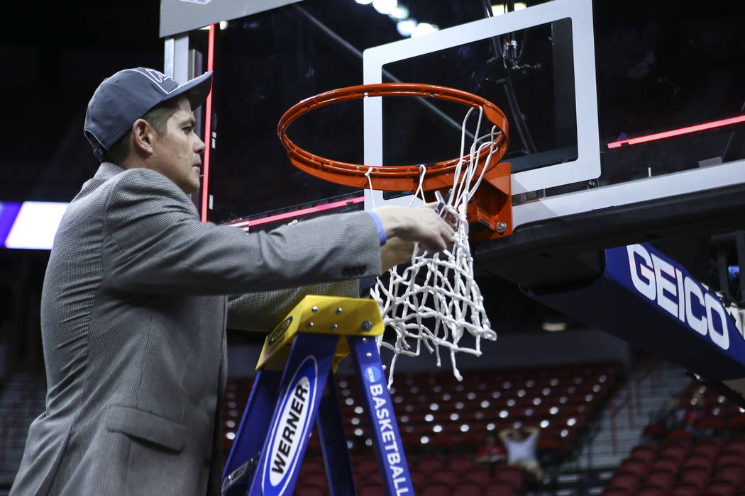 Former UNLV head coach and current UNR assistant coach Dave Rice cuts down the net after defeating Colorado State 79-71 in the Mountain West Conference basketball championship game at the Thomas & ...