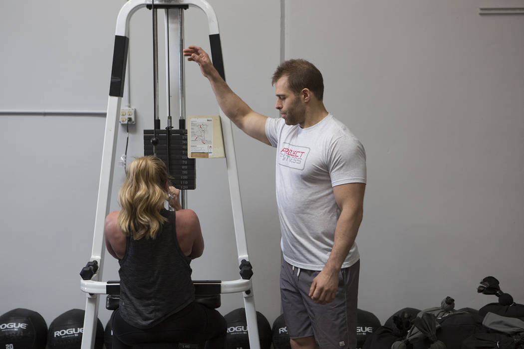 Drew Pollner assists Jay Jay Coulter during a training session at Project Fitness on Wednesday, March 1, 2017, in Las Vegas. Pollner recently opened Project Fitness which includes strength trainin ...