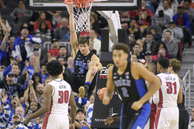 Duke guard Grayson Allen hangs from the rim after a dunk during their NCAA basketball game against UNLV Saturday, Dec. 10, 2016, at the T-Mobile Arena in Las Vegas. Duke won 94-45. Sam Morris/Las  ...