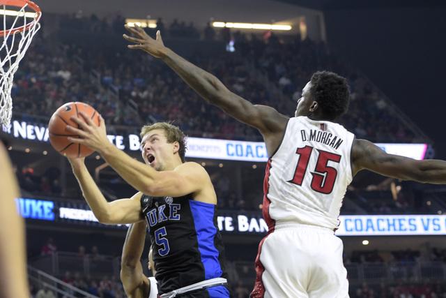 Duke guard Luke Kennard slips under UNLV forward Dwayne Morgan for a basket during their NCAA basketball game Saturday, Dec. 10, 2016, at the T-Mobile Arena in Las Vegas. Duke won 94-45. Sam Morri ...
