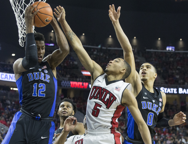 UNLV's Jalen Poyser (5) fights for a rebound with Duke's Javin DeLaurier (12) during the Rebels home matchup with the Blue Devils at T-Mobile Arena on Saturday, Dec. 10, 2016, in Las Vegas. Benjam ...