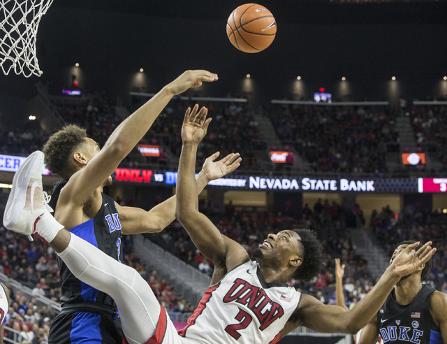 UNLV's Uche Ofoegbu (2) fights for a rebound with Duke's Chase Jeter (2) during the Rebels home matchup with the Blue Devils at T-Mobile Arena on Saturday, Dec. 10, 2016, in Las Vegas. Benjamin Ha ...
