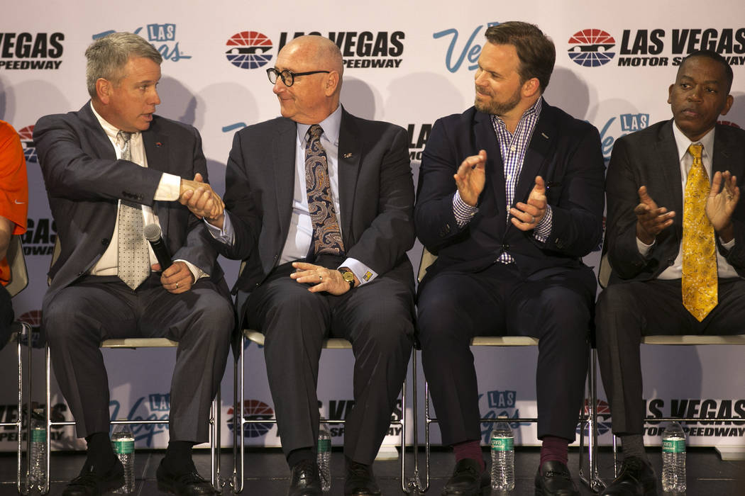General manager of the Las Vegas Motor Speedway Chris Powell, left, shakes the hand of Rossi Ralenkotter, president and CEO of the Las Vegas Convention and Visitors Authority, third from right, du ...