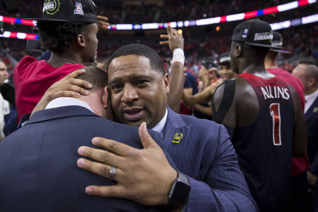 "Arizona Wildcats assistant coach Emanuel ""Book"" Richardson embraces a fellow coach after their team's victory against Oregon Ducks in an NCAA college basketball game for the Pac- ..."