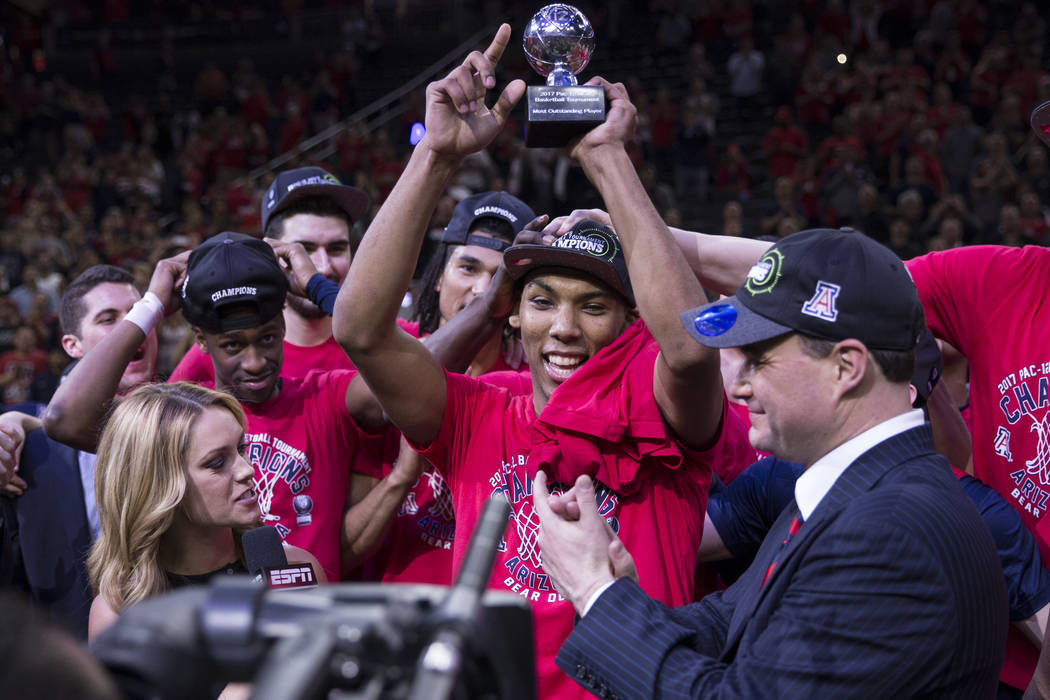 Arizona Wildcats guard Allonzo Trier (35) holds up his most outstanding player trophy after his team's victory against Oregon Ducks in an NCAA college basketball game for the Pac-12 tournament cha ...
