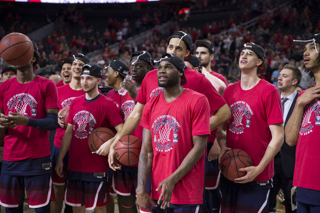 Arizona Wildcats watch as one coach cuts down a net after their victory against Oregon Ducks in an NCAA college basketball game for the Pac-12 tournament championship at T-Mobile Arena Saturday, M ...