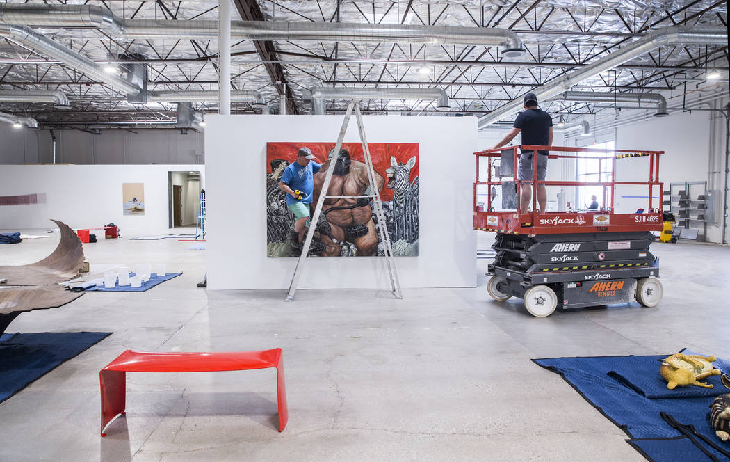 "Brian Byler, middle, and Chris Martin hang a painting at the site of a warehouse pop-up museum at 920 South Commerce Street created to feature the exhibit ""Tilting the Basin"" on  ..."