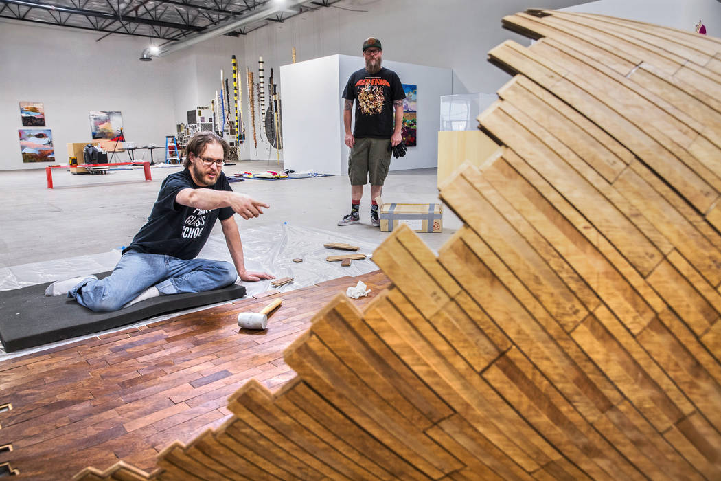 Artists Brent Summerhauser, left, and J.W. Caldwell discuss Summerhauser's custom tongue and groove installation at the site of a warehouse pop-up museum at 920 South Commerce Street created to fe ...