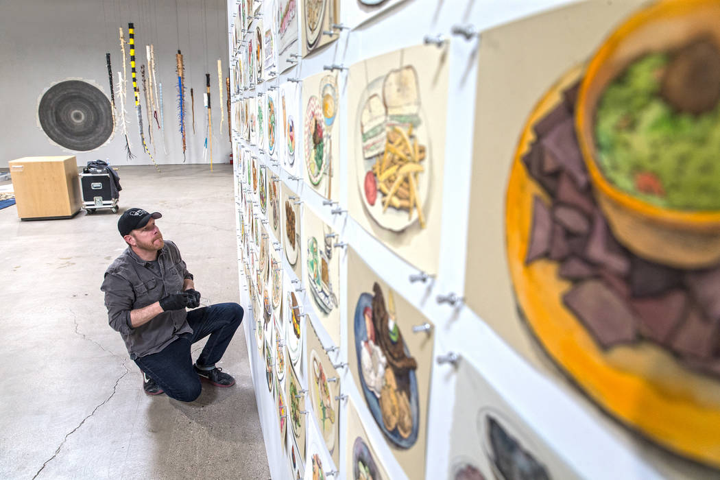 "Artist Mark Brandvik hangs a watercolor installation at the site of a warehouse pop-up museum at 920 South Commerce Street created to feature the exhibit ""Tilting the Basin"" on T ..."