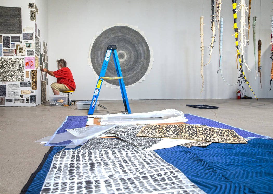 "Artist Galen Brown works on installing a mixed medium piece at the site of a warehouse pop-up museum at 920 South Commerce Street created to feature the exhibit ""Tilting the Basin&quo ..."
