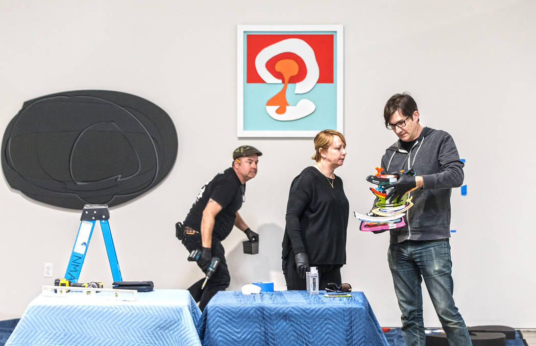 "Sean Hummel, left, Michele Quinn and David Ryan work on an installation at the site of a warehouse pop-up museum at 920 South Commerce Street created to feature the exhibit ""Tilting the B ..."