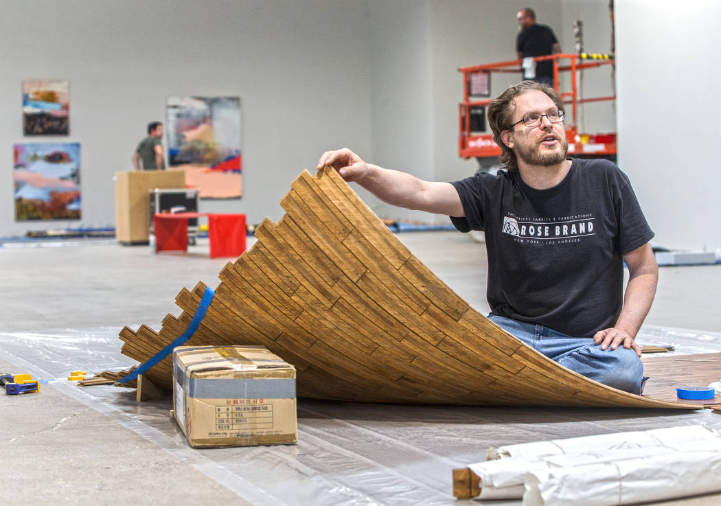 "Artists Brent Summerhauser works on his custom tongue and groove installation at the site of a warehouse pop-up museum at 920 South Commerce Street created to feature the exhibit ""Tilting ..."