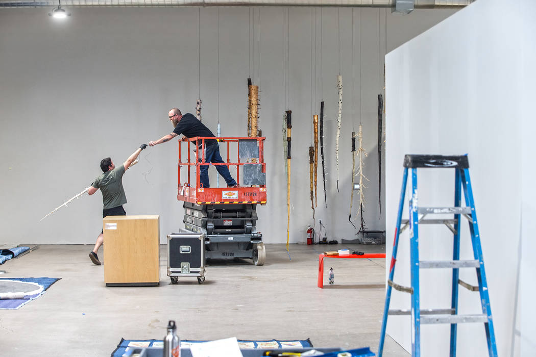 Chris Martin, left, and J.W. Caldwell hang a mixed medium installation piece made of upside down trees by artist Galen Brown at the site of a warehouse pop-up museum at 920 South Commerce Street c ...