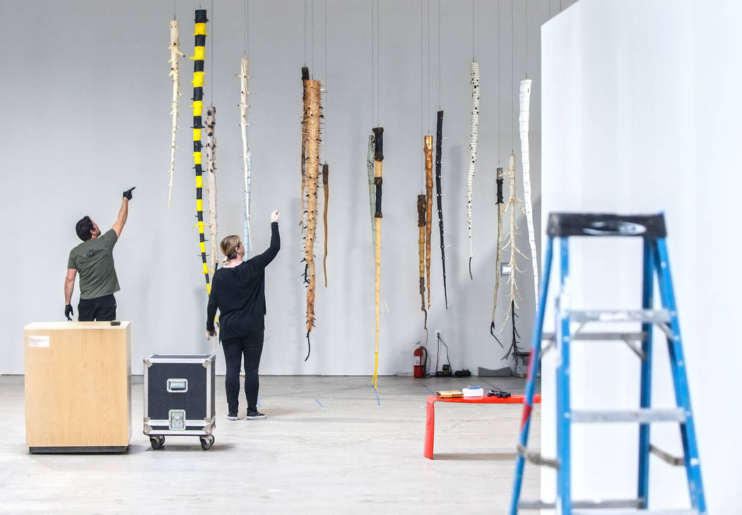 Chris Martin, left, and Michele Quinn hang a mixed medium installation piece made of upside down trees by artist Galen Brown at the site of a warehouse pop-up museum at 920 South Commerce Street c ...