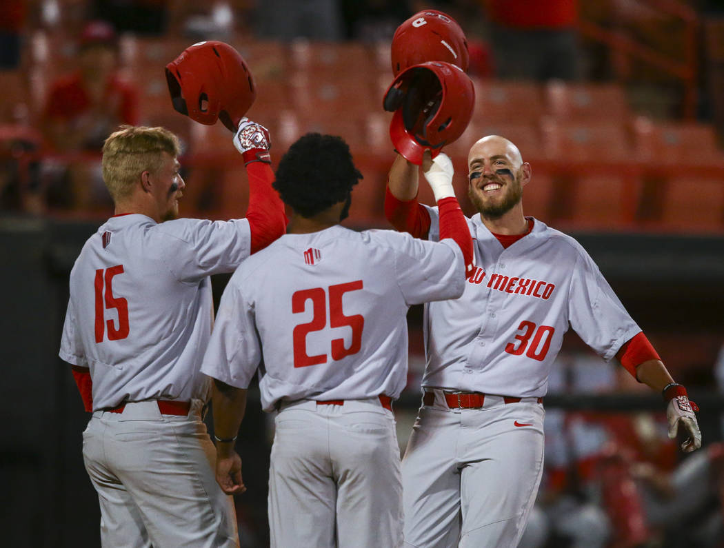 New Mexico infielder Carl Stajduhar (30) celebrates his home run against UNLV with outfielders Andre Vigil (25) and Jared Mang (15) during a baseball game at Wilson Stadium in Las Vegas on Friday, ...