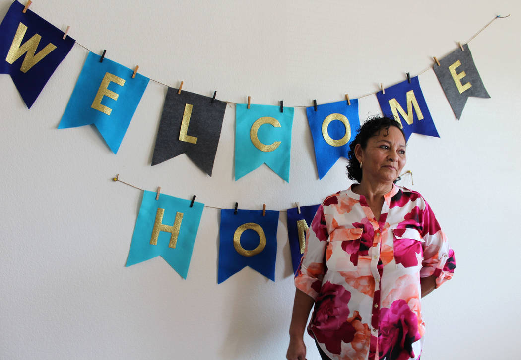Ana Rosas-Hernandez poses with a banner created by Habitat for Humanity in her new home on Thursday, March 9, 2017. Hernandez's home is the latest single-family home project by Habitat for Humanit ...