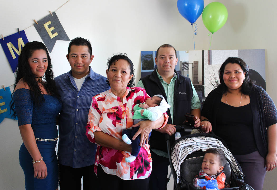 Ana Rosas-Hernandez, center, poses with her youngest grandchild, Moises, inside in her new home on Thursday, March 9, 2017. Standing by her side is Jaime Serrano, left, and his wife Yamileth, and  ...