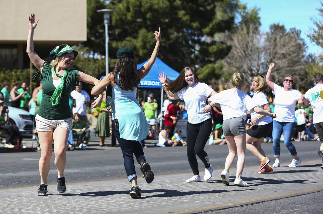 People dance along the parade route during the St. Patrick's Day parade in Henderson on Saturday, March 11, 2017. (Chase Stevens/Las Vegas Review-Journal) @csstevensphoto
