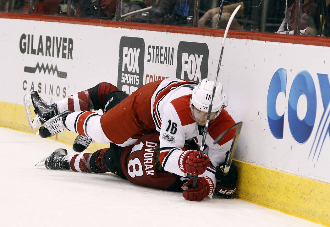 Carolina Hurricanes' Elias Lindholm (16) checks Arizona Coyotes' Christian Dvorak into the boards during the second period of an NHL hockey game, Sunday, March 5, 2017, in Glendale, Ariz. The Hurr ...