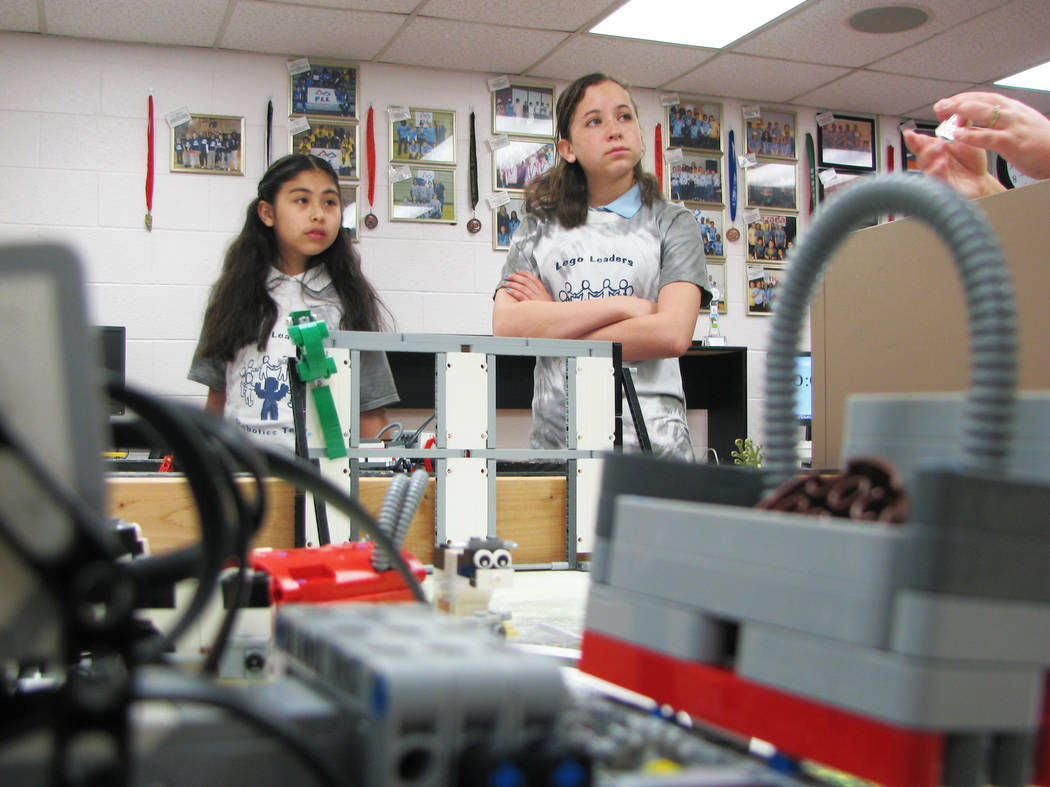 Esmirna Anguiano and Caitlin McKoy of Jo Mackey Academy of Leadership and Global Communication through Technology Lego Leaders team listen to Coach Rachel Kuntz strategize on how to excel at First ...
