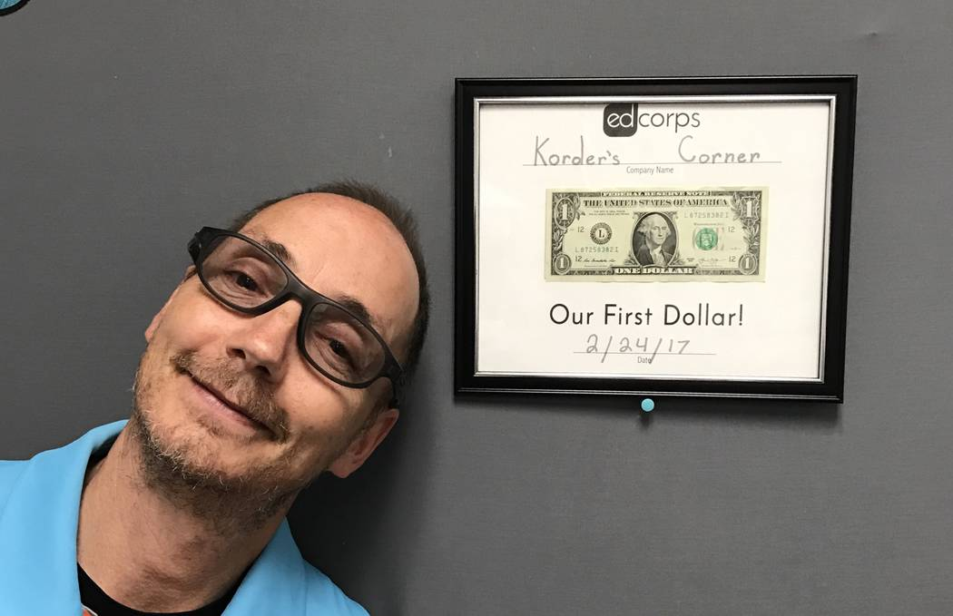 Casey Korder, fifth grade teacher and advisor for Korder's Corner, poses in front of the first dollar that the business earned at Claude & Stella Parson Elementary School. /Courtesy art