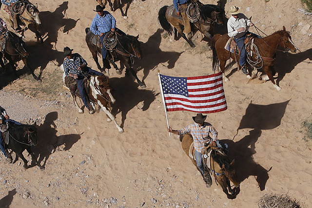 The Bundy family and its supporters fly the American flag as the family's cattle is released by the Bureau of Land Management back onto public land outside of Bunkerville on April 12, 2014. (Jas ...