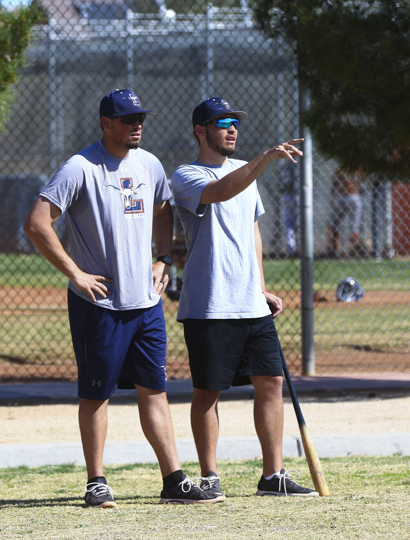 Coach of the varsity Legacy High School baseball team Joey Lauria, left, talks with his brother Nick Lauria, coach of the junior varsity Legacy High School baseball team during practice at Legacy  ...