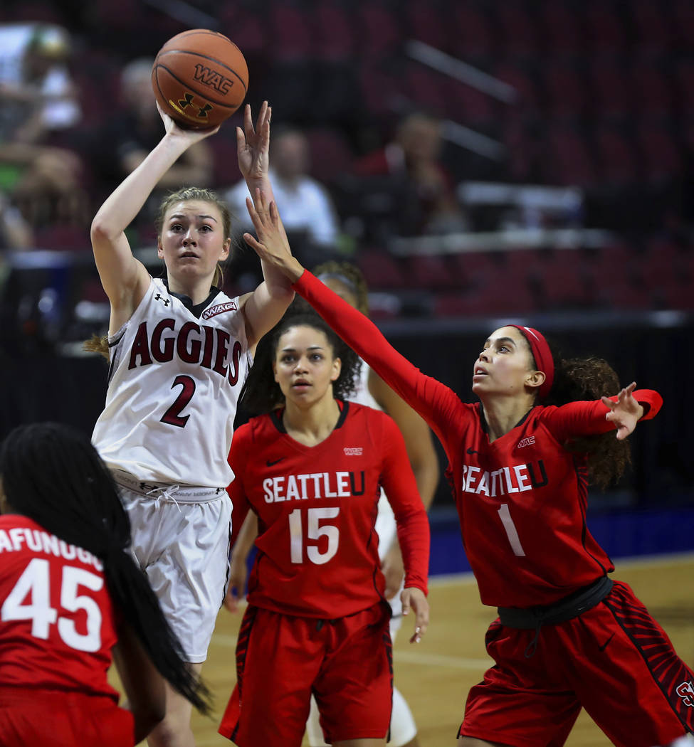 New Mexico State guard Brooke Salas (2) gets off a shot past Seattle University guard Claire Metoyer (1) during the second half of NCAA college basketball game in the final of the Western Athletic ...
