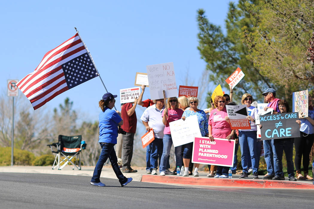 Colleen Brola, 51, walks across Hampton Road during a protest against Sen. Dean Heller, R-Nev., who made an appearance at the Sun City Anthem Center in Henderson on Saturday, March 11, 2017. Helle ...
