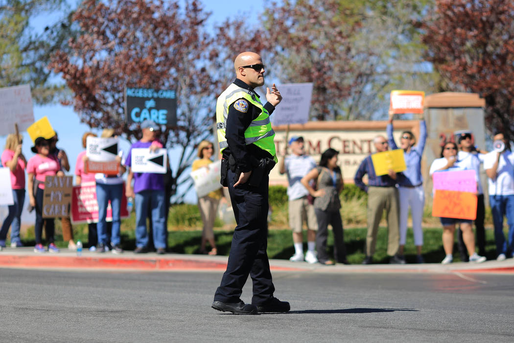 A Henderson police officer directs traffic during a protest against Sen. Dean Heller, R-Nev., who made an appearance at the Sun City Anthem Center in Henderson on Saturday, March 11, 2017. Heller  ...