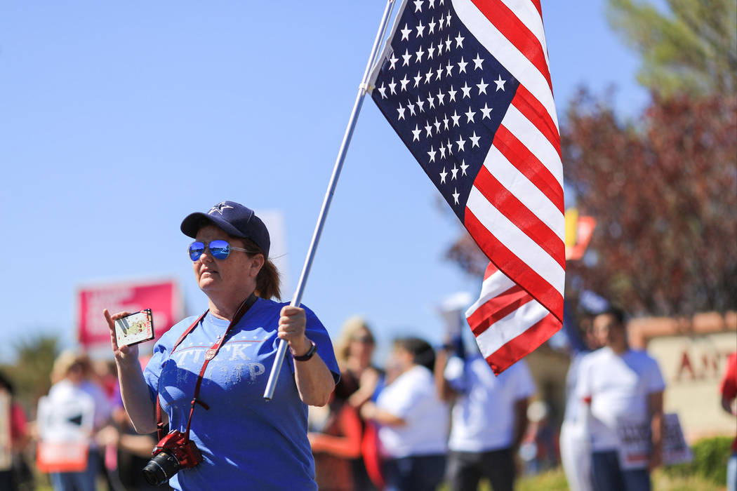 Colleen Brola, 51, carries an upside-down American flag during a protest against Sen. Dean Heller, R-Nev., who made an appearance at the Sun City Anthem Center in Henderson on Saturday, March 11,  ...
