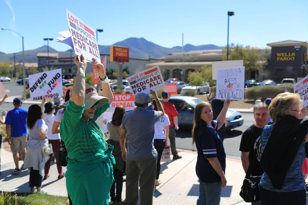 Demonstrators line Hampton Road during a protest against Sen. Dean Heller, R-Nev., who made an appearance at the Sun City Anthem Center in Henderson on Saturday, March 11, 2017. Heller was speakin ...