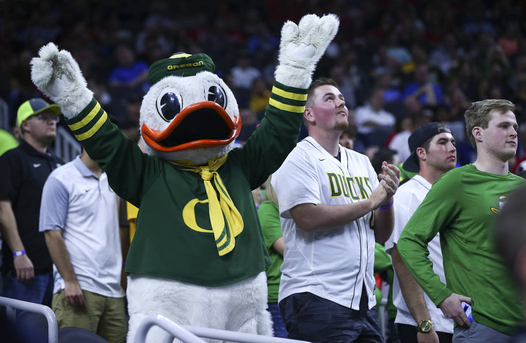 The Oregon Duck cheers with fans during the Pac-12 Conference basketball tournament semifinal game between Oregon and California at the T-Mobile Arena in Las Vegas on Friday, March 10, 2017. (Chas ...