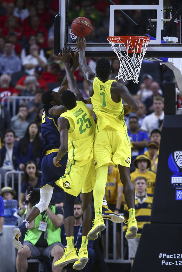 Oregon forwards Jordan Bell (1) and Chris Boucher (25) block a shot from California forward Roger Moute a Bidias (12) during the Pac-12 Conference basketball tournament semifinals at the T-Mobile  ...