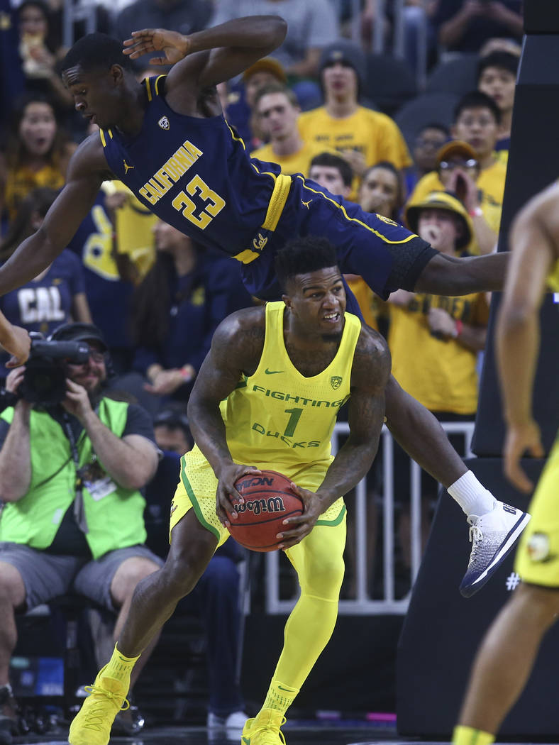 California guard Jabari Bird (23) falls over Oregon forward Jordan Bell (1) during the Pac-12 Conference basketball tournament semifinals at the T-Mobile Arena in Las Vegas on Friday, March 10, 20 ...