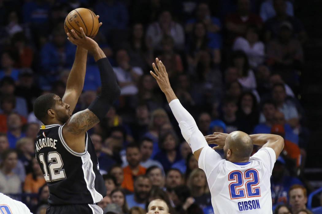 San Antonio Spurs forward LaMarcus Aldridge (12) shoots over Oklahoma City Thunder forward Taj Gibson (22) during the first quarter of an NBA basketball game in Oklahoma City, Thursday, March 9, 2 ...