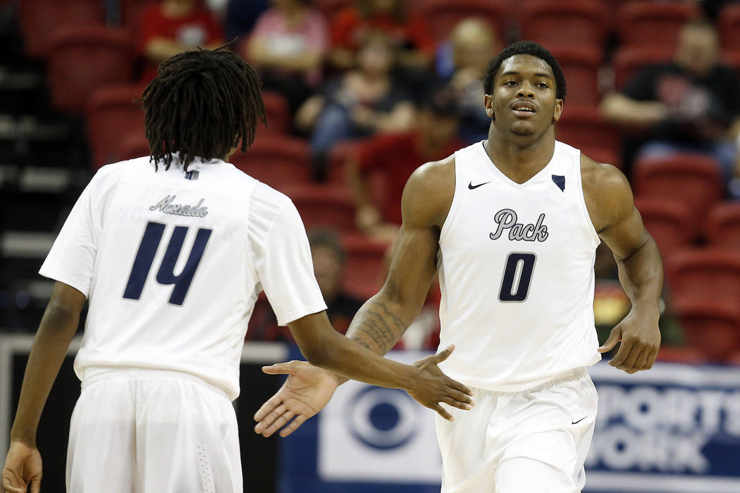 Nevada's Lindsey Drew, left, congratulates teammate Cameron Oliver after a play during the second half of an NCAA college basketball game against Utah State in the Mountain West Conference tournam ...