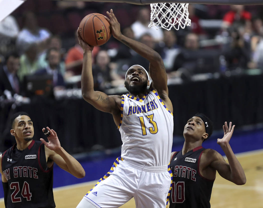 Cal State Bakersfield guard/forward Shon Briggs (13) sets up a shot between New Mexico State guard Matt Taylor (24) and forward Jemerrio Jones (10) during the first half of their NCAA college bask ...