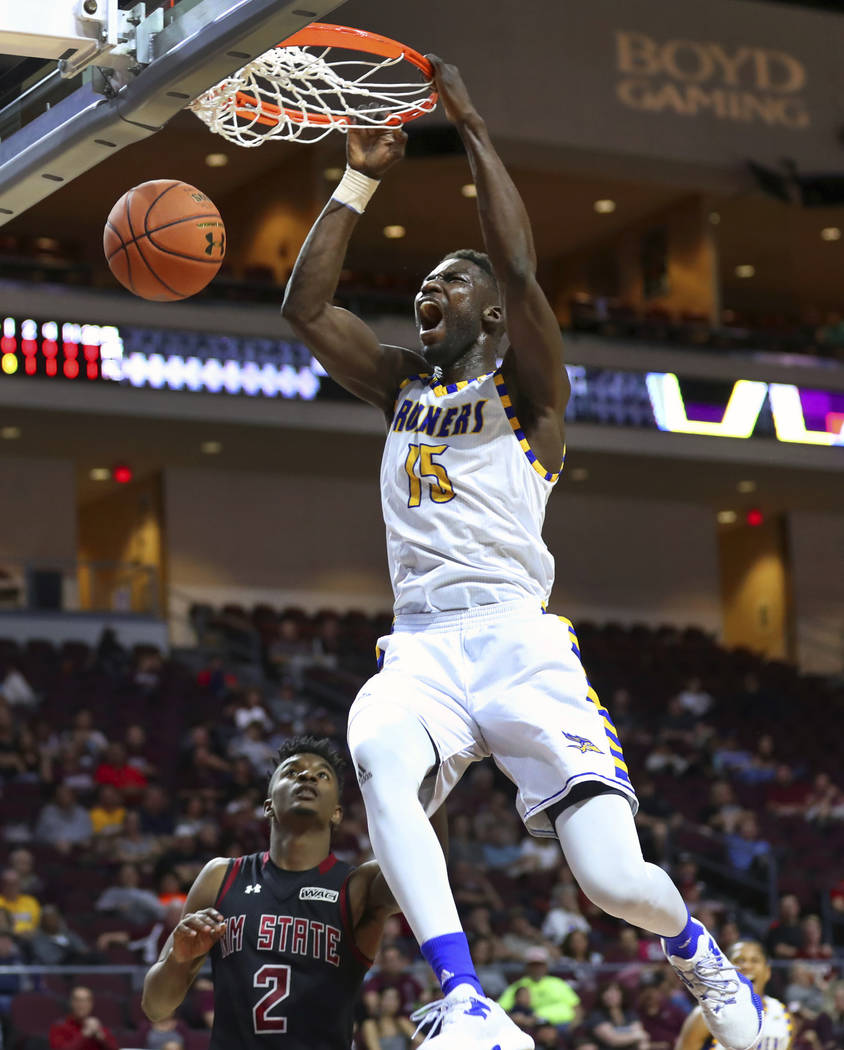 Cal State Bakersfield center Fallou Ndoye dunks over New Mexico State guard Braxton Huggins during the first half of an NCAA college basketball game in the final of the Western Athletic Conference ...